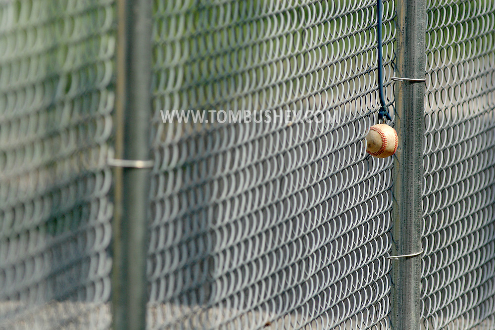 Middletown, NY - A baseball attatched to elastic tubing hangs on the fence at a baseball field  on April 26, 2008.
