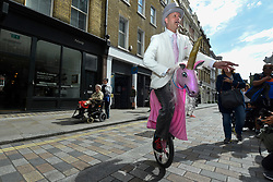 "© Licensed to London News Pictures. 20/06/2019. LONDON, UK.  Unicyclist Guy Collins prepares to take part in the historical ""Rent Ceremony"" in Covent Garden.  A parade of the Covent Garden Area Trust's trustees accompanied by the Lord Mayor of Westminster, Deputy Mayor of Camden and other dignatories as well as a town crier and street entertainers march around the piazza where the trustees pay a symbolic ""peppercorn rent"" consisting of five rosy red apples and five posies of flowers and posies are paid as rent to the landlords.  Photo credit: Stephen Chung/LNP"