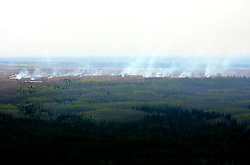CANADA ALBERTA FORT MCMURRAY 10MAY07 - Aerial view of forest fire in the Boreal forest north of Fort McMurray, Alberta, Canada. The Alberta Tar Sands are the largest deposits of their kind in the world and their production is the single largest contributor to Canada's greenhouse gas emissions...Alberta's tar sands are currently estimated to contain a crude bitumen resource of 315 billion barrels, with remaining established reserves of almost 174 billion barrels, thus making Canada's oil resources ranked second largest in the world in terms of size...The industry has brought wealth and an economic boom to the region but also created an environmental disaster downstream from the Athabasca river, polluting the lakes where water and fish are contaminated. The native Indian tribes of the Mikisew, Cree, Dene and other smaller First Nations are seeing their natural habitat destroyed and are largely powerless to stop or slow down the rapid expansion of the oil sands development, Canada's number one economic driver...jre/Photo by Jiri Rezac / WWF-UK..© Jiri Rezac 2007..Contact: +44 (0) 7050 110 417.Mobile: +44 (0) 7801 337 683.Office: +44 (0) 20 8968 9635..Email: jiri@jirirezac.com.Web: www.jirirezac.com..© All images Jiri Rezac 2007 - All rights reserved.