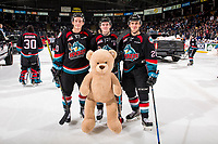 KELOWNA, CANADA - DECEMBER 1: Conner Bruggen-Cate #20, Kyle Topping #24 and Leif Mattson #28 of the Kelowna Rockets pose on the ice with a teddy bear during the annual teddy bear toss against the Saskatoon Blades  on December 1, 2018 at Prospera Place in Kelowna, British Columbia, Canada.  (Photo by Marissa Baecker/Shoot the Breeze)