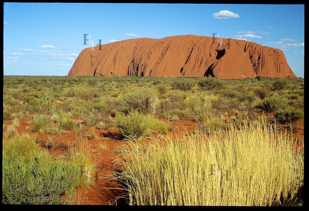 Ayers Rock looms against deep blue sky amid red sands & desert vegetation of Uluru Natl Park. Australia