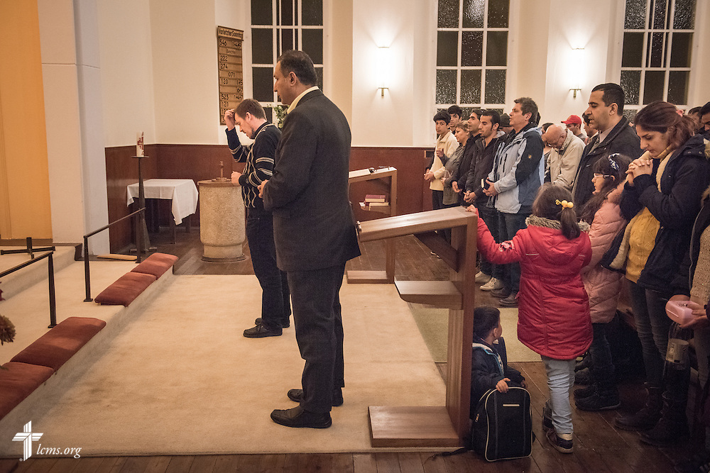 Refugees fill the pews as the Rev. Dr. Gottfried Martens prays at the end of his Bible study class on Saturday, Nov. 14, 2015, at the Dreieinigkeits-Gemeinde, a SELK Lutheran church in Berlin-Steglitz, Germany.  LCMS Communications/Erik M. Lunsford