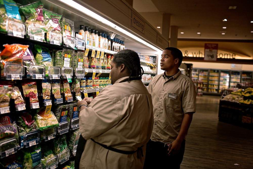 Elio Perdomo, right, finds out what needs to be done in the produce section at a Safeway grocery store in Silver Sping, MD. Perdomo, a student at Montgomery College, tries to take classes in the morning and works up to 16 hours a week at the supermarket.