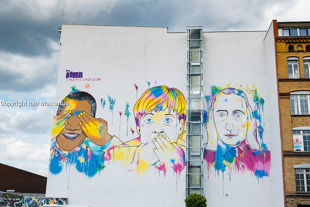 Modern street art mural featuring Barack Obama, Angela Merkel and Vladimir Putin painted on building in Kreuzberg Berlin Germany