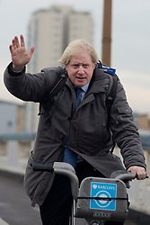 © Licensed to London News Pictures.13/12/2013. London, UK. Mayor of London, Boris Johnson arrives on bicycle to launch the south west expansion of the Barclays Cycle Hire into Hammersmith & Fulham and Wandsworth.Photo credit : Peter Kollanyi/LNP
