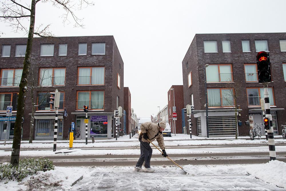 Een man ruimt de sneeuw voor een kruising bij de Amsterdamsestraatweg in Utrecht.<br /> <br /> A man is clearing the road from the snow in Utrecht.