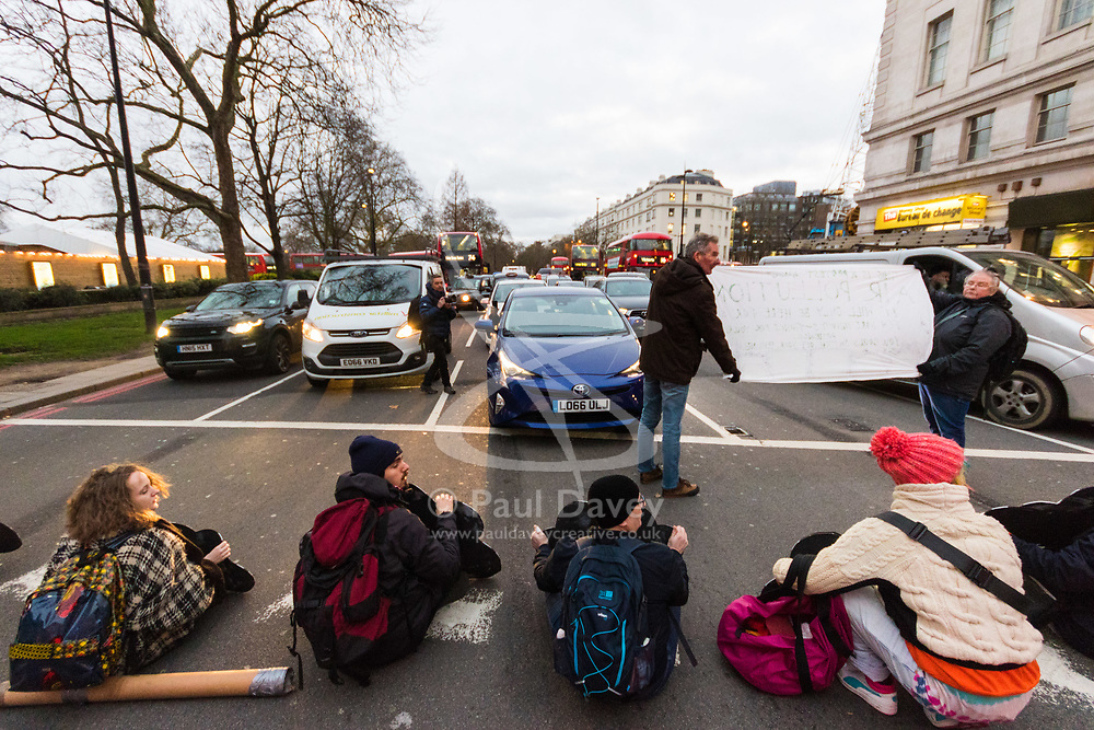 PICTURED: Protesters sit on Oxford Street, causing traffic chaos. Demonstrators from the anti-pollution group Stop Killing Londoners cause traffic chaos for London commuters as they conduct a series of short roadblocks at Marble Arch stopping cars and buses from entering Oxford Street and Park Lane. Irate motorists accused them of creating more pollution than they were stopping, whilst the group said their objectives were long term. A leaflet handed out to motorists says the government is not doing enough to tackle the crisis costing 'taxpayers and the NHS £billions [sic] a year'. PLACE, January 29 2018. © Paul Davey