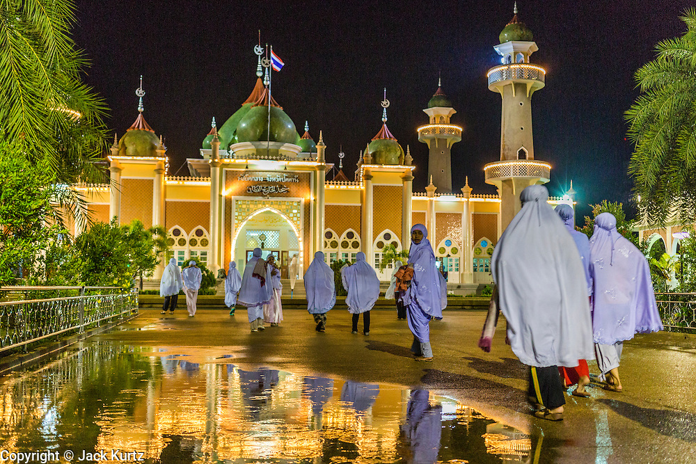 09 JULY 2013 - PATTANI, PATTANI, THAILAND:   Women walk into Pattani Central Mosque in Pattani, Thailand, Tuesday night on the first night of Ramadan. Ramadan is the ninth month of the Islamic calendar, and the month in which Muslims believe the Quran was revealed. Muslims believe that the Quran was sent down during this month, thus being prepared for gradual revelation by Jibraeel (Gabriel) to the Prophet Muhammad. The month is spent by Muslims fasting during the daylight hours from dawn to sunset. Fasting during the month of Ramadan is one of the Five Pillars of Islam.  PHOTO BY JACK KURTZ