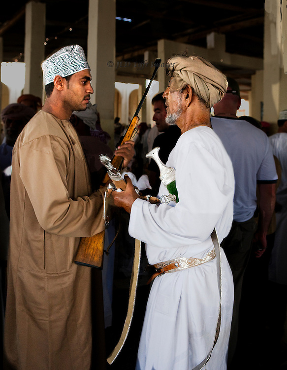 Market day in the Sinaw souk, Oman.  Livestock (goats, camels), vegetables, and weapons on offer.  Men and women shoppers. Two men wearing traditional outfits negotiate the sale and purchase of a rifle and/or a traditional Omani curved dagger.