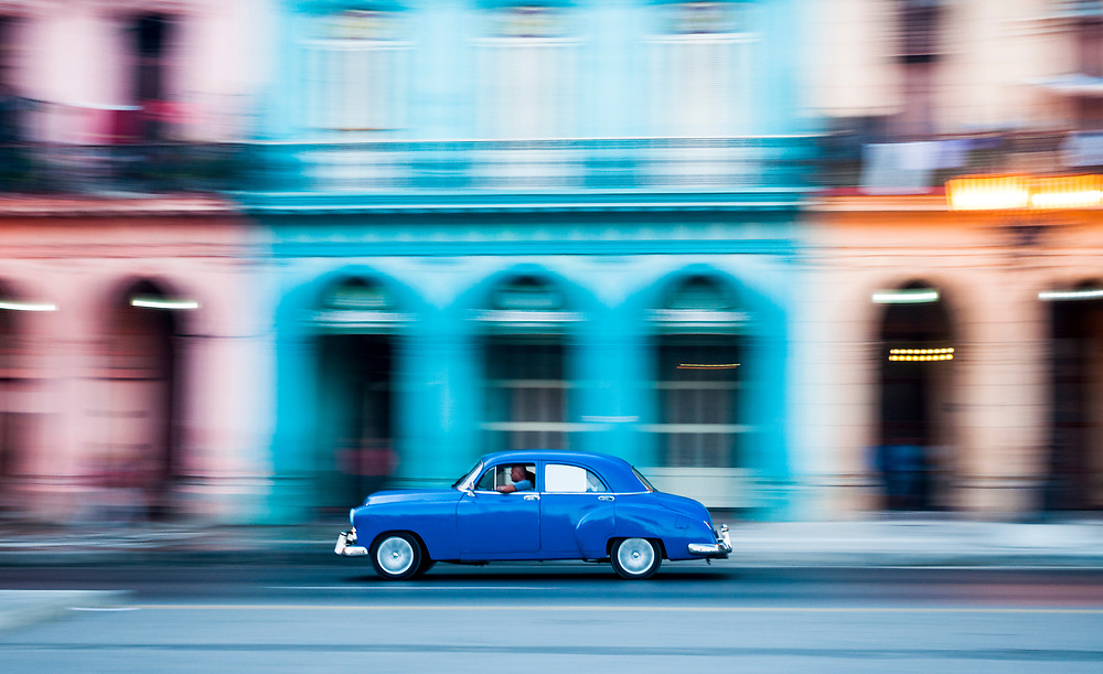A classic car speeds past colorful architecture in Havana, Cuba in a scene that could have just as easily been captured in 1960 as 2017.