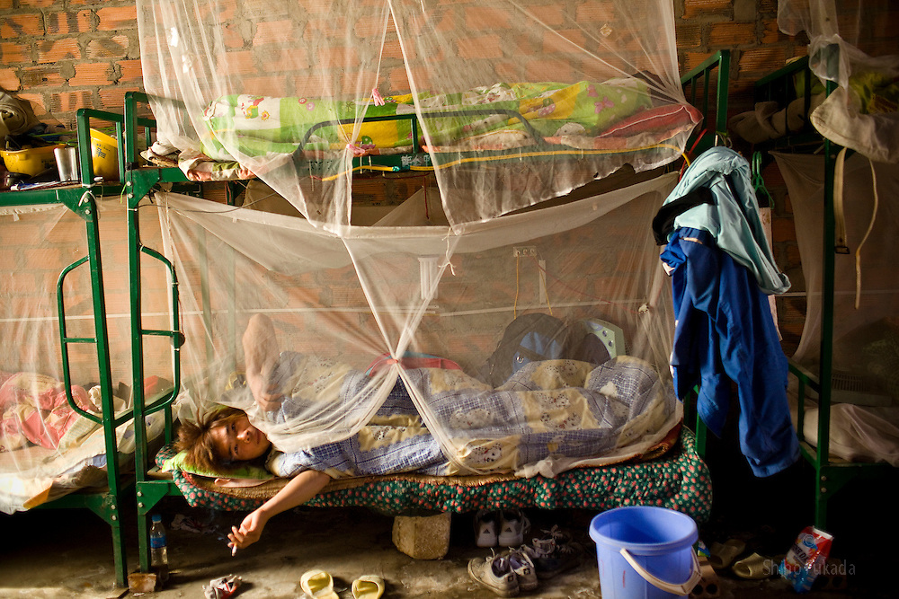 A Chinese worker smokes cigarette in his bunk bed at the dorm near the Haiphong Thermal Power Plant construction site in Trung Son, Vietnam, Nov. 22, 2009. At the construction site here, a few miles northeast of the port city of Haiphong, an entire Chinese world has sprung up, including four walled dormitory compounds for the Chinese workers, restaurants with Chinese signs advertising dumplings and fried rice, and currency exchange shops.