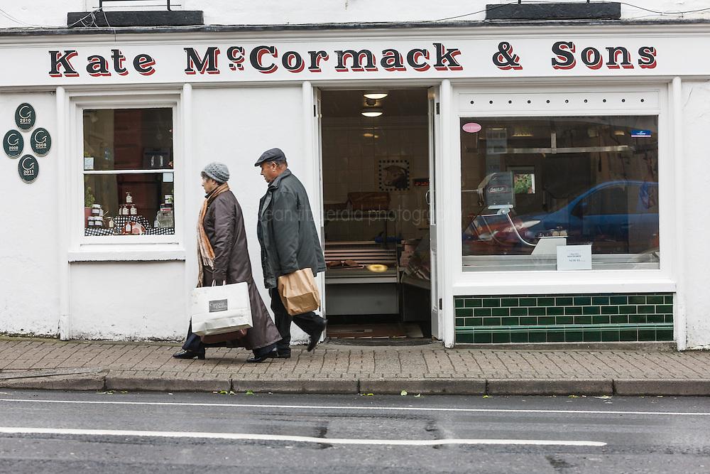 Couple walking past Kate McCormack & Sons butcher shop, Westport, County Mayo, Ireland