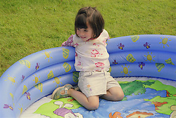 Young girl with autism sitting in empty paddling pool,