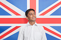Young Asian man in shirt day dreaming against British flag