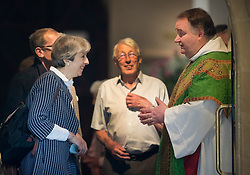 © Licensed to London News Pictures. 18/06/2017. Reading, UK. Prime Minister Theresa May and her husband Philip talk to the Reverend Jamie Taylor (R) as they attend church in her constituency. Photo credit: Peter Macdiarmid/LNP