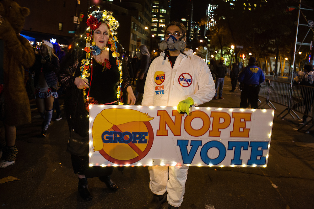 "New York, NY - 31 October 2016. Two people walk behind a sign that reads Grope Nope Vote, the ""grope"" behind the international red slashed circular symbol meaning ""no"", and with a caricature of Donald Trump's hair capping the circle."
