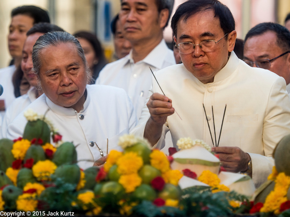 """04 SEPTEMBER 2015 - BANGKOK, THAILAND: PHRAMAHARAJAGURUPHITISRIVISUTTHIKUN (left), the Royal Priest of the Royal Household of Thailand, guides VEERA ROJPOJANARAT, the Minister of Culture for Thailand, through prayers at the Erawan Shrine Friday. A """"Holy Religious Ceremony for Wellness and Prosperity of our Nation and Thai People"""" was held Friday morning at Erawan Shrine. The ceremony was to regain confidence of the Thai people and foreign visitors, to preserve Thai religious customs and traditions and to promote peace and happiness inThailand. Repairs to Erawan Shrine were completed Thursday, Sept 3 after the shrine was bombed on August 17. Twenty people were killed in the bombing and more than 100 injured. The statue of the Four Faced Brahma in the shrine was damaged by shrapnel and a building at the shrine was damaged by debris.     PHOTO BY JACK KURTZ"""