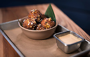 Street corn fritters featuring oaxaca and cotija cheese, roasted poblanos, and an elote mayo dipping sauce at Bartaco restaurant at Hilldale Shopping Center in Madison, WI on Thursday, April 18, 2019.