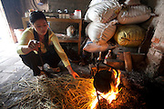 The daughter-in-law of rice farmer Nguyen Van Theo boils water with rice straw fuel at their shared homestead in Tho Quang village, Vietnam. (From the book What I Eat: Around the World in 80 Diets.)