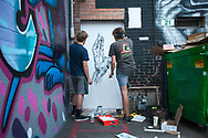 Tyler Crabb and Jacob Bottles in front of their mural late in the evening of August 5, 2017 during the Freak Alley Gallery seventh annual mural event in downtown Boise, Idaho. <br /> <br /> Represents the pierced hand of Christ.<br /> <br /> Freak Alley Gallery's week long event provided an &quot;art-in-motion&quot; experience as it welcomed the public to watch artists work on their murals.