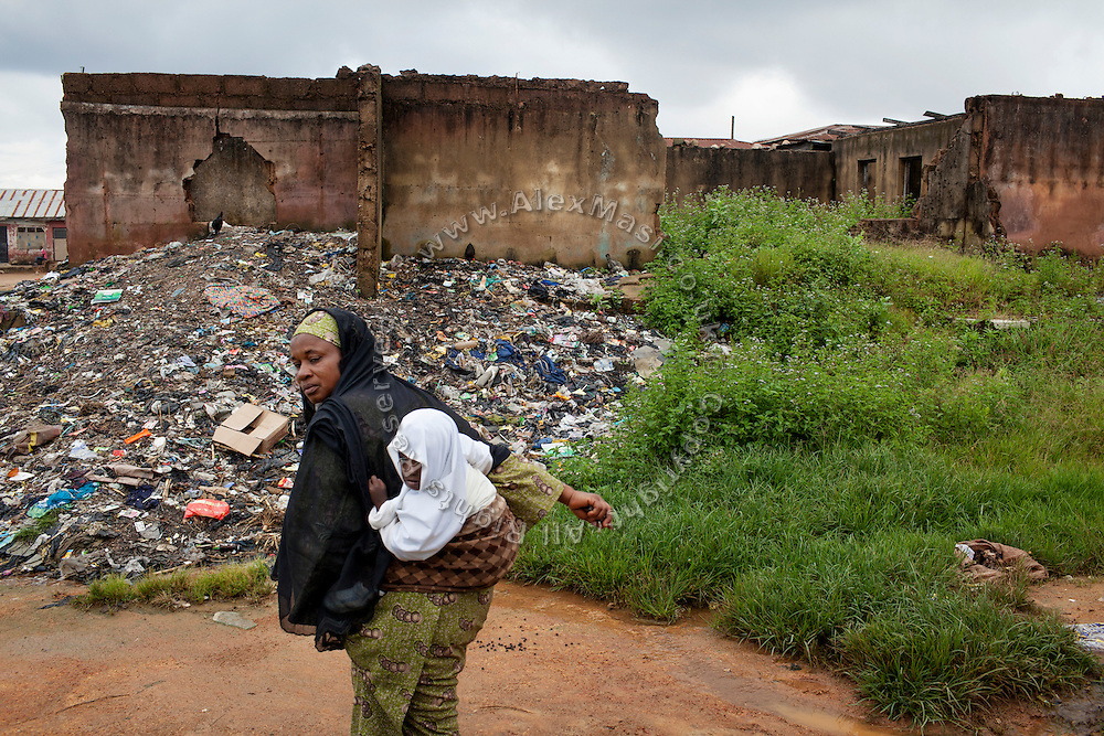 A Muslim woman and her child are walking by a pile of garbage next to a series of destroyed homes in Dutse Uku, pop. 40.000, a Muslim-dominated neighbourhood in Jos, Plateau State, Nigeria. Residents of Dutse Uku clashed and were attacked by a neighbouring Christian community after local government elections in 2008. 380 houses were destroyed, and around 20 people were killed. All Christians have since then left their homes within the community, in order to resettle in Christian-dominated areas of the city.