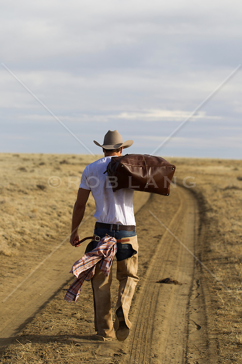 cowboy carrying a bag over his shoulder as he walks down a dirt road on a ranch in New Mexico