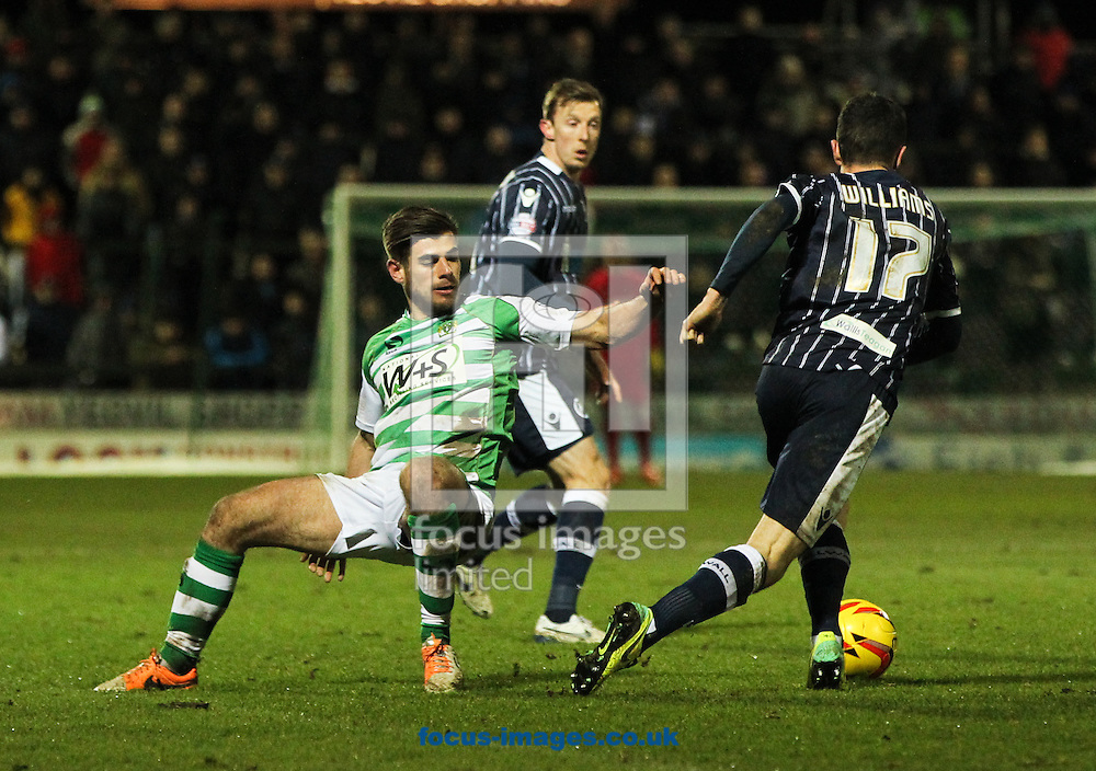 Joe Edwards (left) of Yeovil Town loses his footing as Shaun Williams (right) of Millwall takes the ball on during the Sky Bet Championship match at Huish Park, Yeovil<br /> Picture by Tom Smith/Focus Images Ltd 07545141164<br /> 11/02/2014