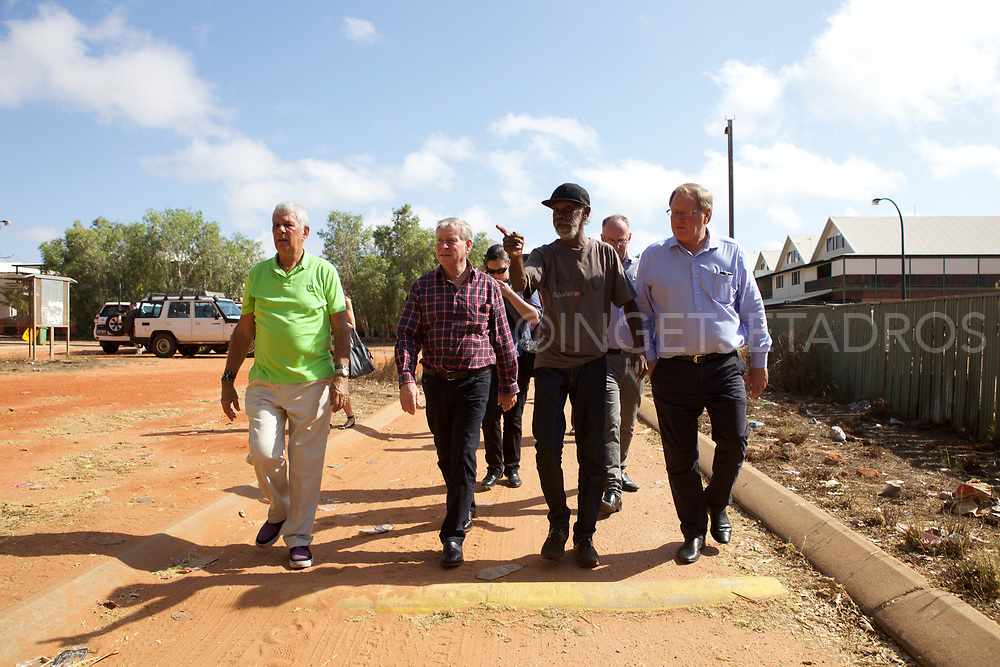 "Rodney Wiggan (2nd R) showing Colin Barnett, (2nd L) Premier of Western Australia, his community Kennedy Hill, a small Aboriginal Community, in the town centre of Broome. Colin Barnett recently announced that over 100 Aboriginal Communities will be closed in WA due to lack of funding. ""This community looks well under control"" was one of the Premier's comments. Mallingbarr (Kennedy Hill) community. Broome, Western Australia"