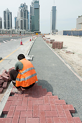 Worker laying block paving footpath in Dubai United Arab Emirates