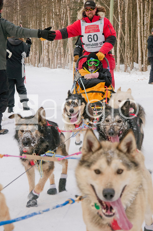A hand waits to greet musher Matt Giblin and his Iditarider along the Chester Creek Trail during the 2011 Iditarod Ceremonial Start.