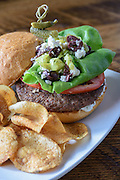 The Greek Burger on a brioche bun with feta cheese, lettuce, tomato, black olives and pepperoncini with Tzatziki sauce and served with house-made chips at Somewhere restaurant at 1135 Bardstown Road, next to Nowhere bar. July 26, 2016