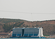 KUMGANG<br /> THE NORTH KOREAN GHOST TOWN<br /> <br /> The first town USA will find on his way to invade NK will be this ghost town where HUnday lost 1 billion USD..<br /> <br /> The Mount Kumgang tourist complex in North Korea, near the DMZ, was built in 1998 by the South Korean giant company Hyundai. The chaebol paid a fee of $1 billion to the North Korean government for 50 years of exclusivity. The cost of the 500-square kilometer complex was $400 million, including hotels, a spa, a fire station, a tourism office, a golf course, a supermarket, a clinic, tours in the mountain... Kumgang resort attracted nearly 2 millions south korean tourists from1998 to 2008.<br /> In July 2008 a South Korean tourist, Miss Park Wang-ja, was shot dead there and South Korea decided to stop all the tours in North Korea. The North Korean government said the tourist entered the military zone, and ignored the warnings from the north korean soldiers.<br /> So in retaliation, North Korea decided to seize the whole tourist complex. This decision was a real drama. Not for the touristic industry only, but for the separated families from the south and the north: Kumgang was also the place where hundreds of North and South Korean relatives were meeting each other for the first time in decades.<br /> For those reasons, since 2008, Mount Kumgang complex has became a ghost town. Only very few western tourists could visit the area.<br /> <br /> Photo shows:   Haegeumgang floating hotel. The 90 meter floating structure has travelled over 13000 km to arrive in North Korea. Its original location was in the Great Barrier Reef, then it moved to Vietnam and in 2000 Hyundai decided to use it for the Kumgang Tourism Project. 20 millions dollars lost in this hotel.<br /> ©Eric Lafforgue/Exclusivepix Media