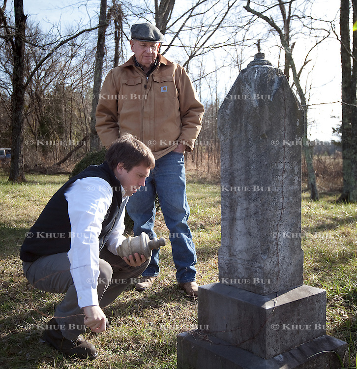 John W. Sanderson (age 75, brown coat); William I. Sanderson &ndash; goes by Bill (age 40, blue fleece vest), son of John W. Sanderson look over a head stone in need of repair during a visit to the private family cemetery Thursday, December 22, 2016, in Cartersville, VA.  The private cemetery contains 4 named graves, but the family believes there are more family members buried here as there are more stones next to the named grave sites.<br /> <br /> Photo by Khue Bui for the New York Times