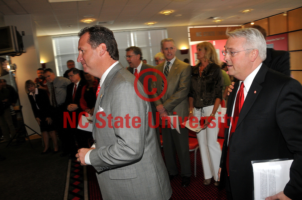 Mark Gottfried and Chancellor Randy Woodson (right) head to the stage during the press conference introducing Gottfried as the new NC State men's basketball coach.