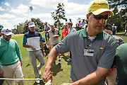 Gallery guard Hayes Thompson of Charlotte, NC, moves the ropes to allow Bubba Watson and Brandeb Grace to pass to the second tee during teh first round of the 2016 Masters Tournament. Hayes, whose father has worked fourteen Masters, is working at the tournament for teh second time after writing letters of application for eight years. Golf: 2016 Masters<br /> Round 1 Thursday<br /> Augusta National/Augusta, GA, <br /> 04/07/2016<br /> SI-14 TK1<br /> Credit: Darren Carroll