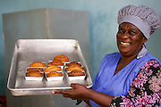 Joyce Marwa holding up a tray of freshly baked cakes from the oven.<br /> <br /> Joyce set up and now runs a bakery that bakes bread and cakes. She also processes nutritious flour (a mix of 5 grains)<br /> <br /> She attended MKUBWA enterprise training run by the Tanzania Gatsby Trust in partnership with The Cherie Blair Foundation for Women.
