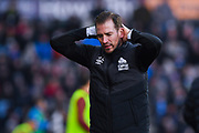 Jan Siewert of Huddersfield Town (Manager) looks down with his hands on his head during the Premier League match between Huddersfield Town and Arsenal at the John Smiths Stadium, Huddersfield, England on 9 February 2019.