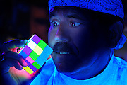 A man closely inspects a glowing Rubiks cube.Black light