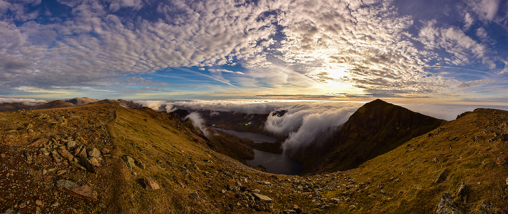 """Snowdon (Welsh: Yr Wyddfa, pronounced[ər ˈwɪðva]) is the highest mountain in Wales, at an elevation of 1,085 metres (3,560ft) above sea level, and the highest point in the British Isles outside the Scottish Highlands. It is located in Snowdonia National Park (Parc Cenedlaethol Eryri) in Gwynedd, and has been described as """"probably the busiest mountain in Britain"""". It is designated as a national nature reserve for its rare flora and fauna.<br /> The rocks that form Snowdon were produced by volcanoes in the Ordovician period, and the massif has been extensively sculpted by glaciation, forming the pyramidal peak of Snowdon and the arêtes of Crib Goch and Y Lliwedd. The cliff faces on Snowdon, including Clogwyn Du'r Arddu, are significant for rock climbing, and the mountain was used by Edmund Hillary in training for the 1953 ascent of Mount Everest.<br /> The summit can be reached by a number of well-known paths, and by the Snowdon Mountain Railway, a rack and pinion railway opened in 1896 which carries passengers the 4.7 miles (7.6km) from Llanberis to the summit station. The summit also houses a cafe called Hafod Eryri, open only when the railway is operating and built in 2006 to replace one built in the 1930s. The railway generally operates to the summit station from Whitsun to October. The daily running schedule depends on weather and customer demand."""