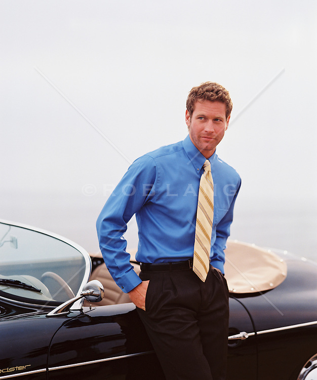 Well dressed man in a shirt and tie standing against his convertible with his hands in his pockets