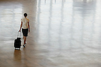 Woman walking with wheeled suitcase elevated back view.