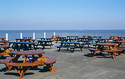 AF5GRF Empty tables and chairs suggesting slack business by the seaside in traditioanl British seaside pier.