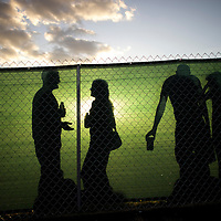 A boyfriend and girlfriend are silhouetted in front of a fence during the Governors Ball Music Festival on Randall's Island in New York, NY on June 6, 2014.