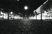 En lyktestolpe lyser opp brosteinen mens biler kj&oslash;rer forbi i gaten p&aring; dette nattbildet fra Berlin.<br /> <br /> Berlin street photography 2010. Gatefotografi fra Berlin i 2010.<br /> <br /> Foto: Svein Ove Ekornesv&aring;g