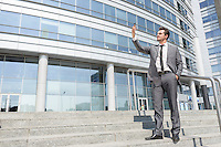 Full length of businessman taking self portrait on steps outside office
