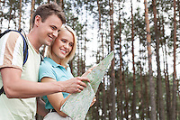 Happy young backpackers looking at map in woods