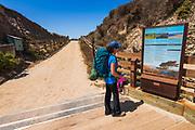 Hiker and interpretive sign at Bechers Bay, Santa Rosa Island, Channel Islands National Park, California USA