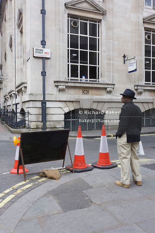 A man stands still on a street corner by three traffic diversion cones