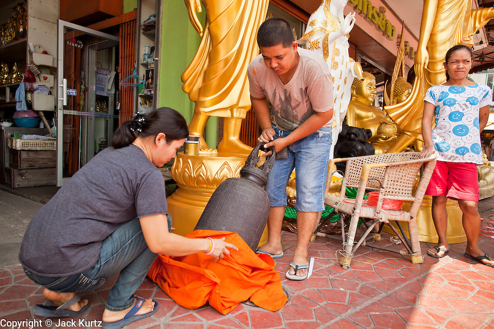 "05 JULY 2011 - BANGKOK, THAILAND:   Merchants wrap a bell in a saffron cloth before moving it to a Buddhist temple in front of their store on Bamrung Muang Street in Bangkok. Thanon Bamrung Muang (Thanon is Thai for Road or Street) is Bangkok's ""Street of Many Buddhas."" Like many ancient cities, Bangkok was once a city of artisan's neighborhoods and Bamrung Muang Road, near Bangkok's present day city hall, was once the street where all the country's Buddha statues were made. Now they made in factories on the edge of Bangkok, but Bamrung Muang Road is still where the statues are sold. Once an elephant trail, it was one of the first streets paved in Bangkok, it is the largest center of Buddhist supplies in Thailand. Not just statues but also monk's robes, candles, alms bowls, and pre-configured alms baskets are for sale along both sides of the street.          PHOTO BY JACK KURTZ"