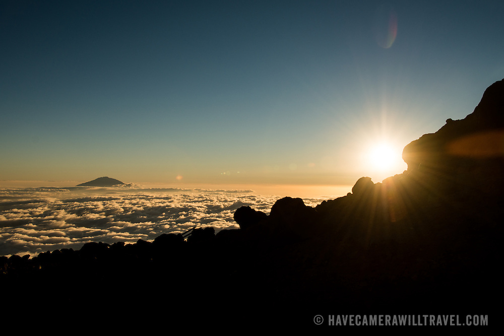 The summit of Mt Meru pokes through the clouds while the sun sets on the horizon as seen from Arrow Glacier on Mt Kilimanjaro's Lemosho Route.